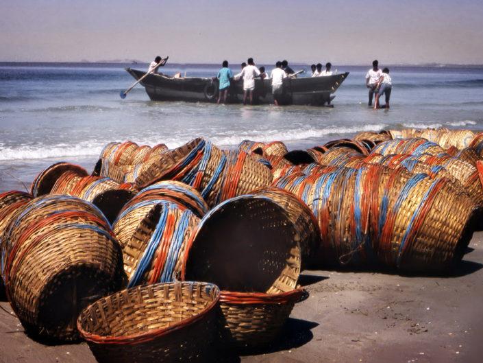 Pescatori Indiani si preparano ad uscire con le ceste colorate sulla spiaggia di Goa